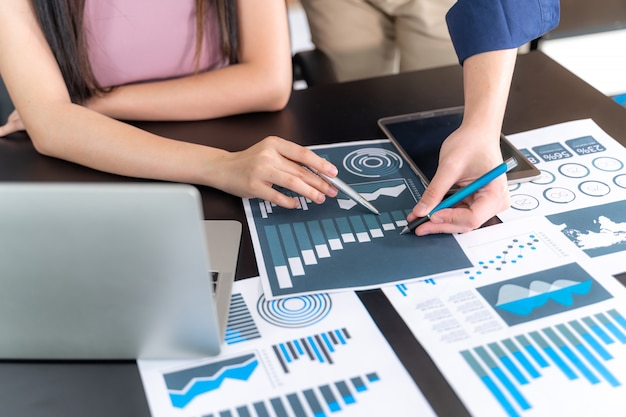 Cerrar la mano del gerente de marketing empleado apuntando al documento comercial durante la discusión en la sala de reuniones, cuaderno en la mesa de madera - concepto de negocio