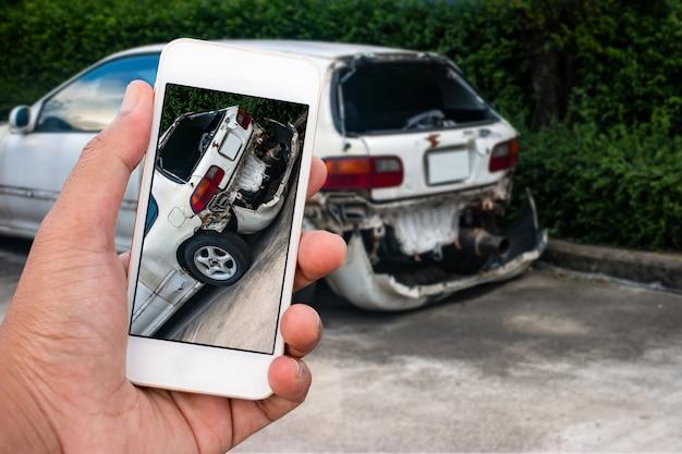 Cerrar la mano del hombre que sostiene el teléfono inteligente y tomar una foto del accidente de coche