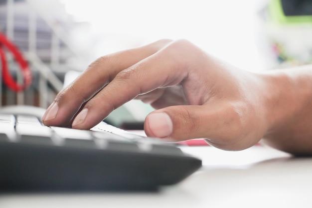 Cerrar la mano del hombre con teclado y pantalla srceen antiguo. concepto de oficina de trabajo. trabajo de concepto serio y ocupado. concepto de asalariado.