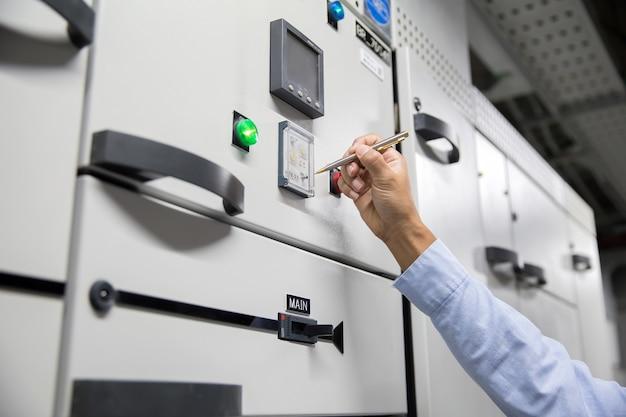 Cerrar la mano del ingeniero eléctrico comprobando el voltaje de la corriente eléctrica