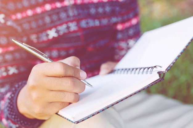 Cerrar la mano joven están sentados con bolígrafo escribiendo bloc de notas de conferencia de registro en el libro sobre la mesa de madera.