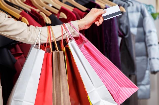 Cerrar la mano de la mujer con muchos bolsos de compras y tarjeta de crédito