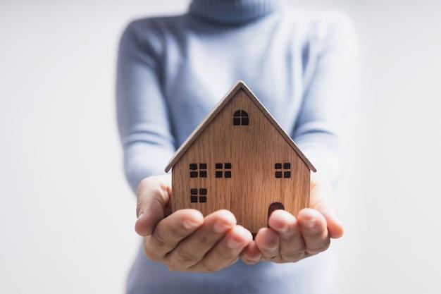 Cerrar la mano de la mujer que sostiene la casa modelo, tener hogar y familia feliz y concepto de bienes raíces