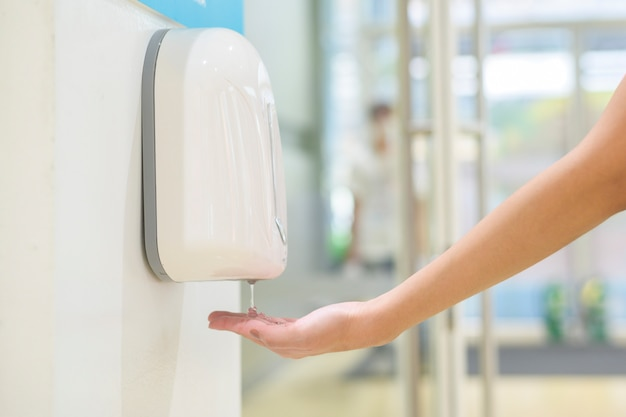 Cerrar mano de mujer está utilizando gel de alcohol en el centro comercial