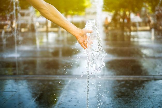 Cerrar la mano de la persona toque la fuente de agua en la calle de verano al aire libre