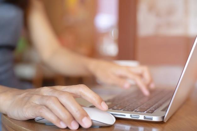 Cerrar mano personas persona mujer en computadora portátil mediante teléfono móvil sentarse en el piso de madera.