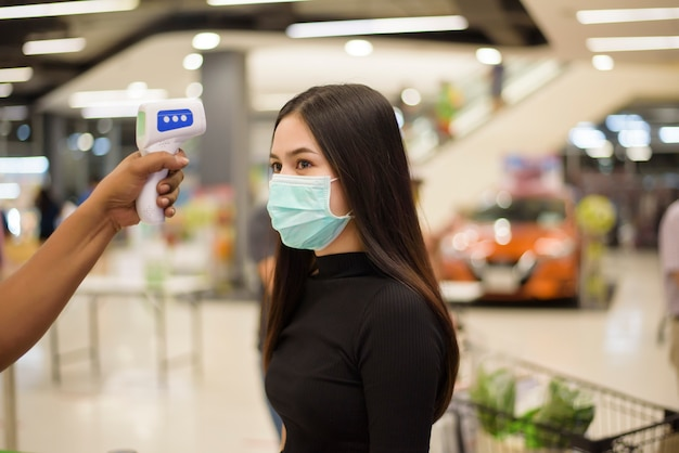 Cerrar una mano con pistola de temperatura con una mujer joven, medida de distanciamiento social para la prevención de covid-19 en el centro comercial
