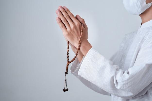 Cerrar mano sosteniendo un abalorios musulmanes o tasbih con gris