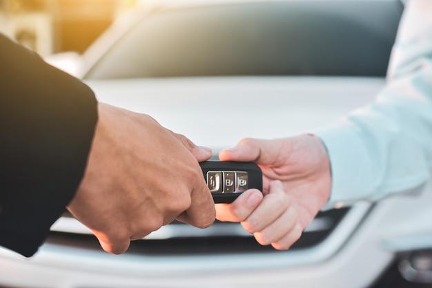 Cerrar una mano sosteniendo el concepto clave del coche de venta, dar y tomar el coche clave