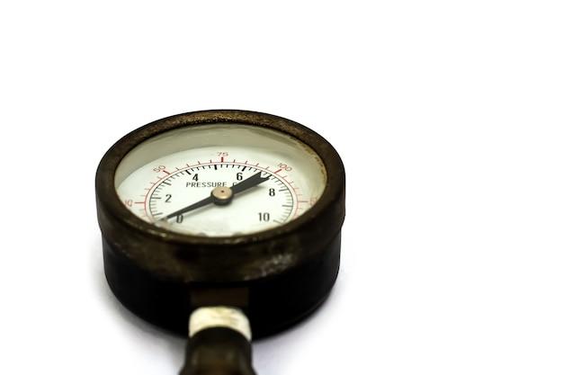 Cerrar manómetro viejo y oxidado aislado sobre fondo blanco.