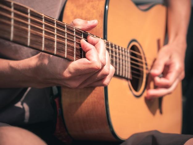 Cerrar las manos en las cuerdas de una guitarra zurda