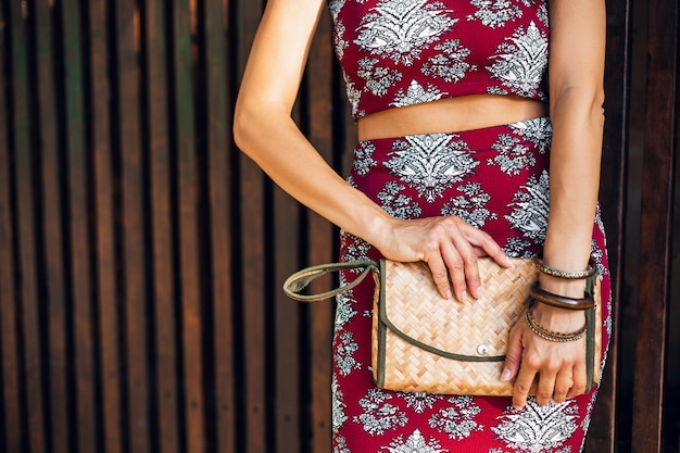 Cerrar las manos de la elegante mujer sosteniendo el bolso de paja