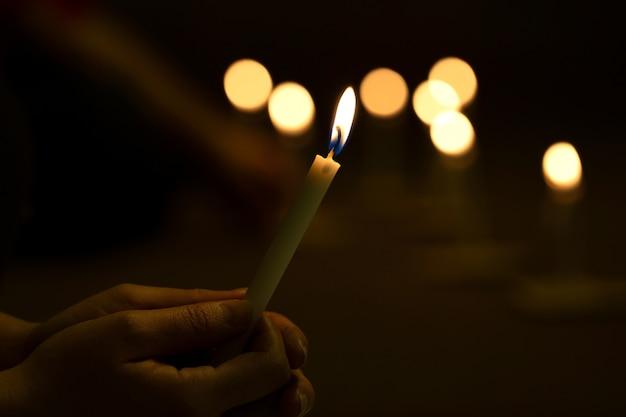 Cerrar las manos encendiendo vigilia vela en la oscuridad