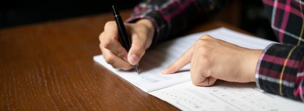 Cerrar las manos de los estudiantes anotar notas musicales en clase en la escuela