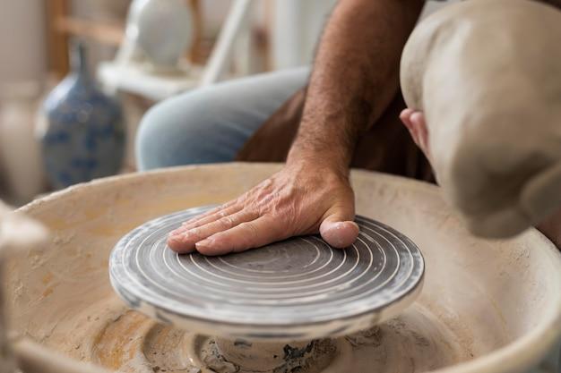 Cerrar las manos haciendo cerámica