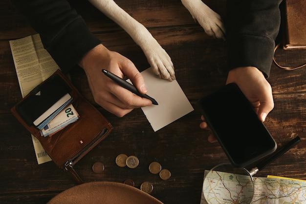 Cerrar las manos del hombre sostienen el teléfono inteligente y escribe el plan de ruta de la aventura en una hoja de papel sobre una mesa de madera envejecida
