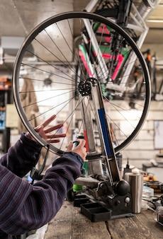 Cerrar las manos inflando la rueda de la bicicleta