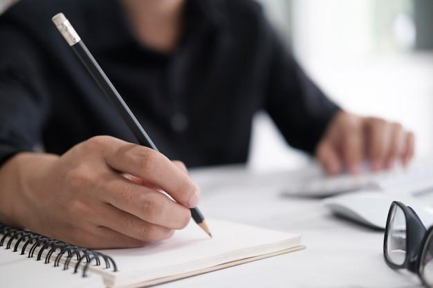 Cerrar las manos con lápiz escribiendo en el cuaderno. concepto de educación.
