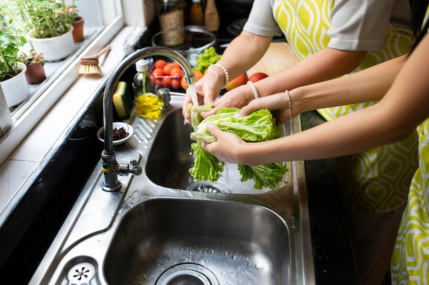 Cerrar las manos lavando verduras