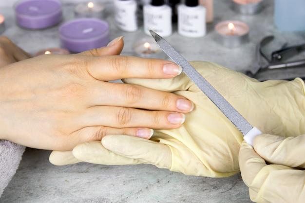 Cerrar las manos de manicurista en guantes con una lima de uñas sosteniendo las manos del cliente