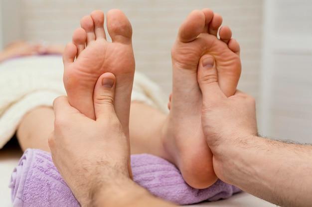 Cerrar las manos masajeando las plantas de los pies