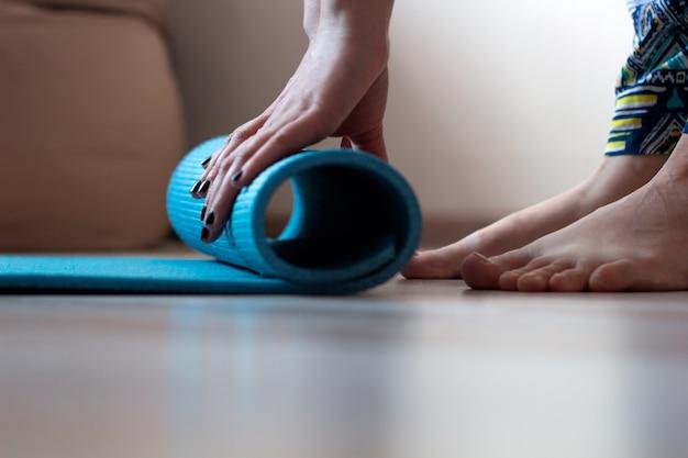 Cerrar las manos de la mujer con estera de yoga en casa