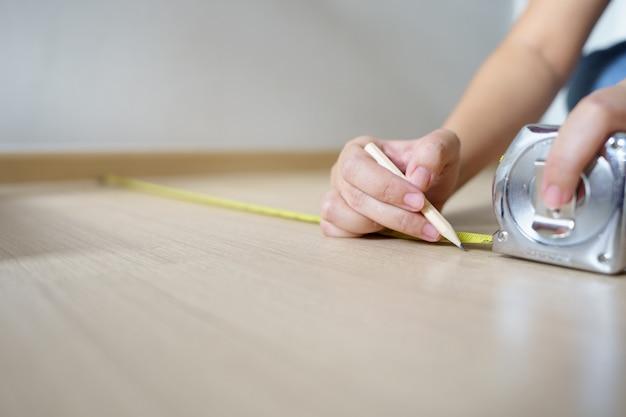 Cerrar manos mujer ingeniero con cinta amarilla de carpinteros