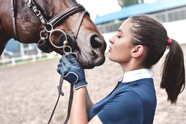 Cerrar las manos de la mujer jinete abrazando a un caballo. niña acariciando a su caballo en el establo.