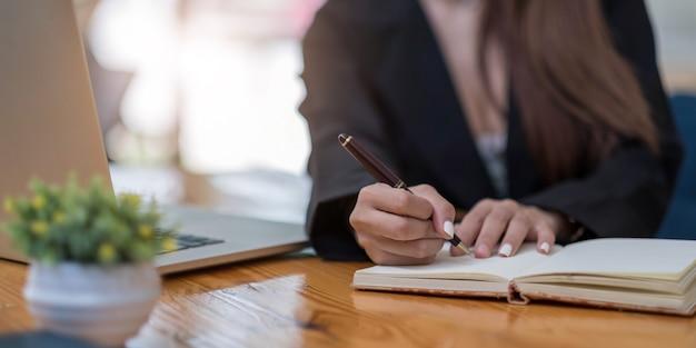 Cerrar las manos de la mujer con ordenador portátil, cuaderno y bolígrafo tomando notas en la oficina de negocios