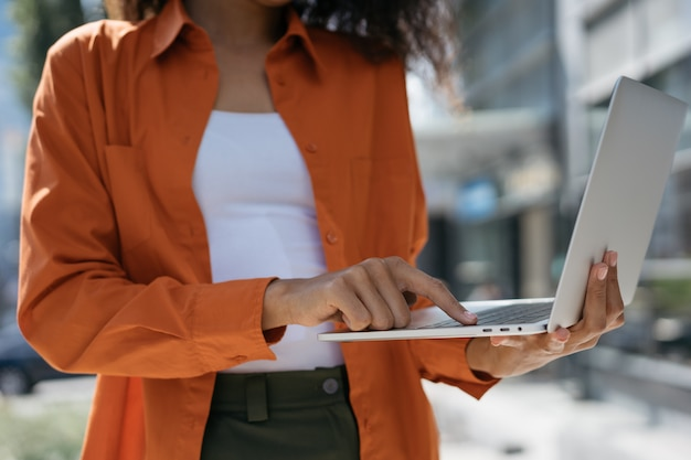 Cerrar las manos de la mujer usando la computadora portátil para comprar en línea, reservar boletos, realizar transacciones