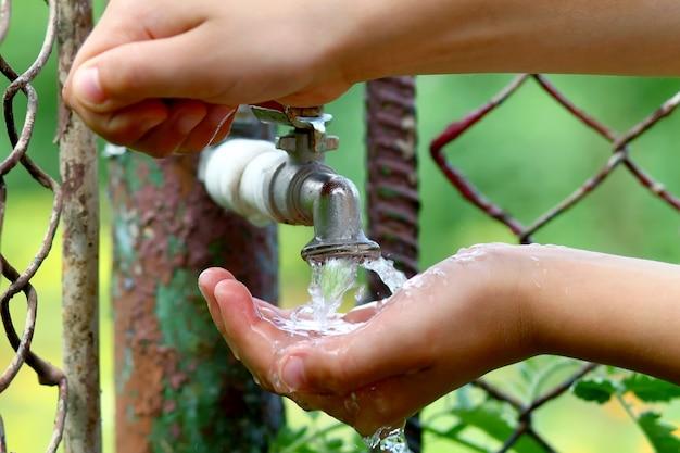 Cerrar las manos del niño con gotas de agua del grifo de latón antiguo grunge