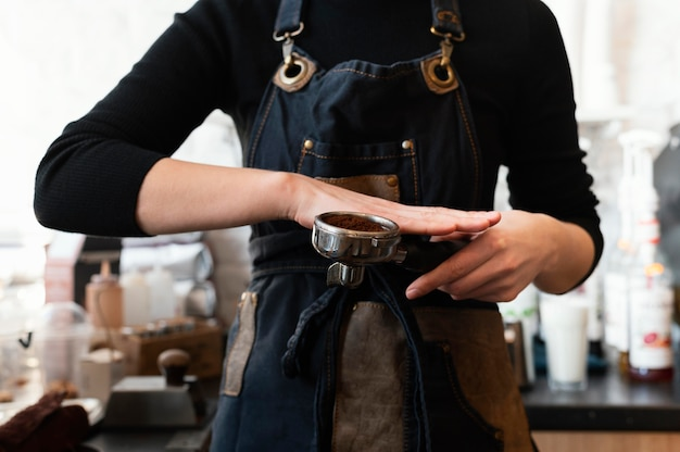 Cerrar las manos preparando café