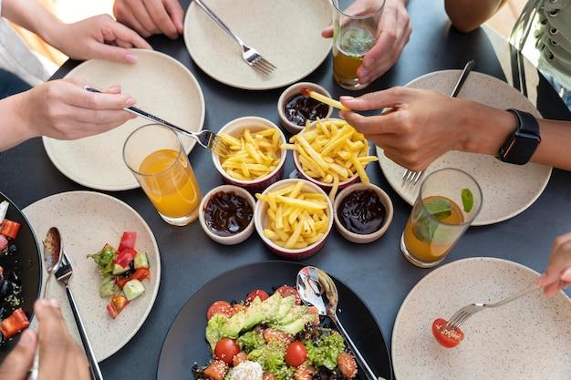 Cerrar las manos sosteniendo la comida y los tenedores