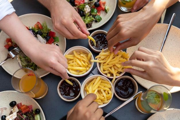 Cerrar manos sosteniendo papas fritas