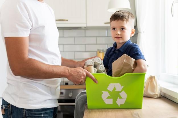 Cerrar las manos sosteniendo la papelera de reciclaje