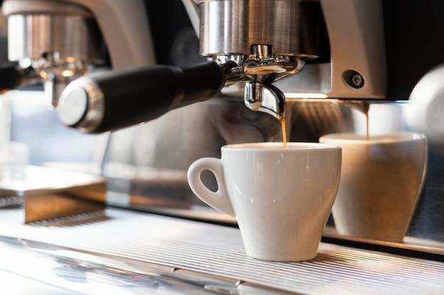 Cerrar máquina vertiendo café en taza