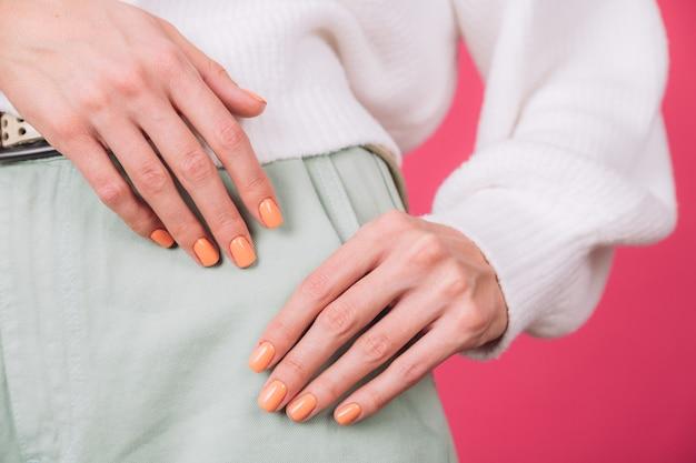 Cerrar el marco de las manos de la mujer con manicura naranja en suéter blanco y pared rosa