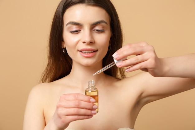 Cerrar morena mujer medio desnuda con piel perfecta, maquillaje desnudo aplicar aceite de botella en la cara aislada en la pared de color beige pastel