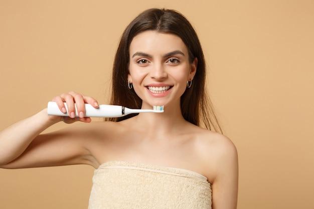 Cerrar morena mujer medio desnuda con una piel perfecta, maquillaje desnudo mantenga pincel aislado en la pared de color beige pastel