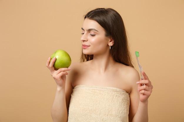 Cerrar morena mujer medio desnuda con piel perfecta, maquillaje desnudo sostiene pincel aislado en pared beige pastel