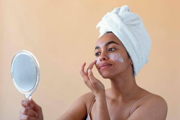 Cerrar mujer aplicando crema facial