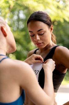 Cerrar mujer ayudando a competidor