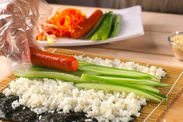 Cerrar mujer chef con guantes de plástico proceso de preparación de sushi enrollado