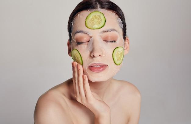 Cerrar mujer gentil sofisticada en una máscara hidratante con un pepino fresco en la cara en la belleza seria con los ojos cerrados y la mano derecha cerca de la cara