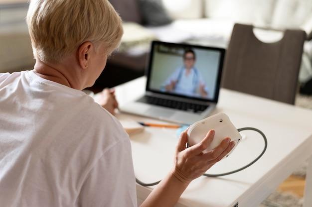 Cerrar mujer hablando con el médico en línea