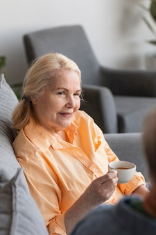Cerrar mujer jubilada sosteniendo la taza
