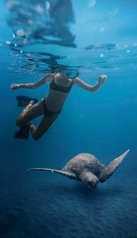 Cerrar mujer nadando con tortuga