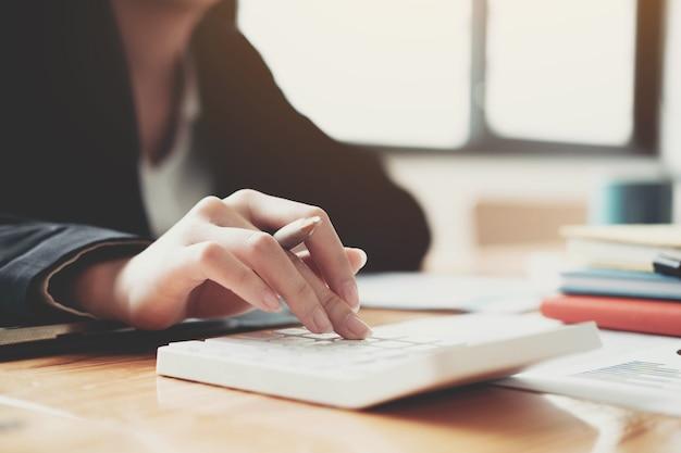 Cerrar mujer de negocios con calculadora y portátil para hacer finanzas matemáticas en un escritorio de madera en la oficina