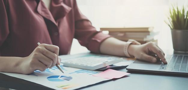 Cerrar mujer de negocios usando laptop y comprobando un gráfico en un escritorio de madera en la oficina
