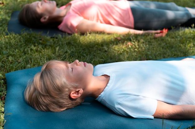 Cerrar mujer y niño meditando